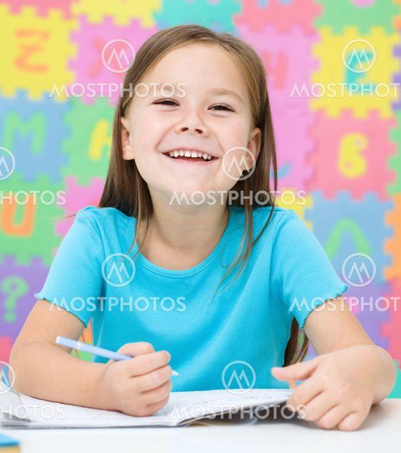 Pieni tyttö kirjoittaa kynällä