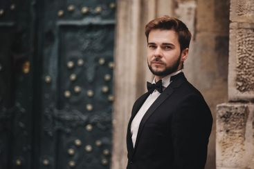portrait of a stylish young groom in an old European...