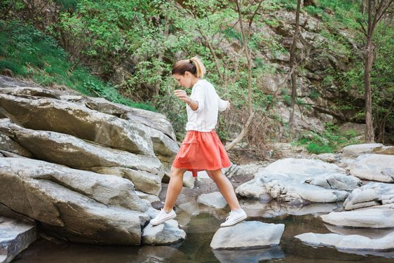 Young woman jumping over the creek
