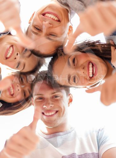 group of smiling teenagers looking down