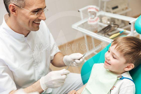 Smiling dentist doing dental treatment to little boy