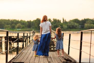 mom and kids in blue clothes standing old bridge