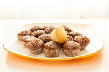 Tasty chocolate muffins with one cake muffin on top