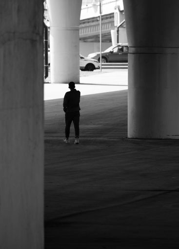 A human silhouette among giant concrete pillars under a...