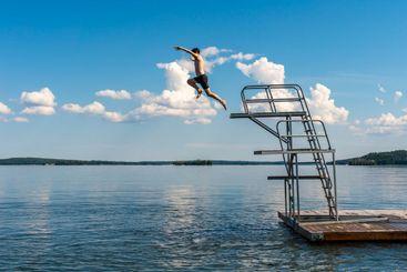 Ung man hoppar dyker från ett hopptorn i sjön.