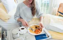 Patient in hospital lying in bed eating meal