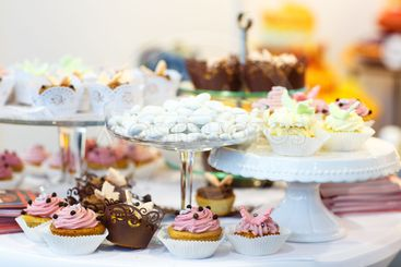 Elegant sweet table with cupcakes, cake pops and candy on...