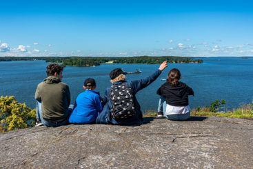 Familj på berg ser på utsikt över vatten.