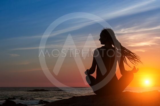 Silhouette woman yoga on the beach at amazing sunset....