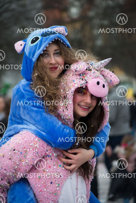 o girls wearing a unicorn costume smiling in the street...