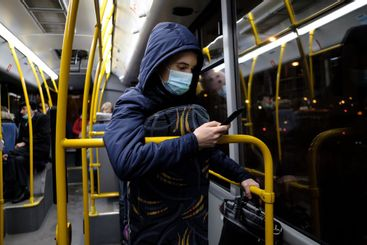 A man in a medical mask with a smartphone in his hands...