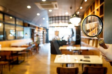 Magnifying glass with cafe restaurant with abstract blur...