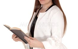 Teenage girl standing white jacket holding a book in hands