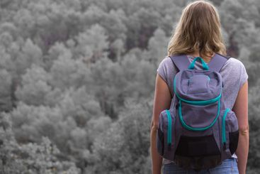 Woman with backpack in the forest. Half black and white.