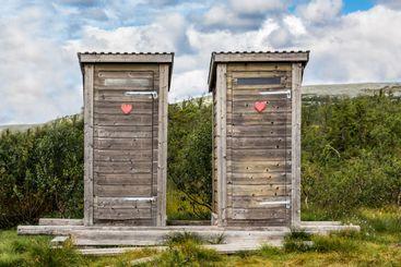 Två utedass i vildmarken svenska fjällen.