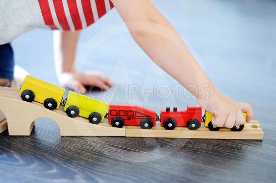 Toddler boy playing with toy wooden train at home