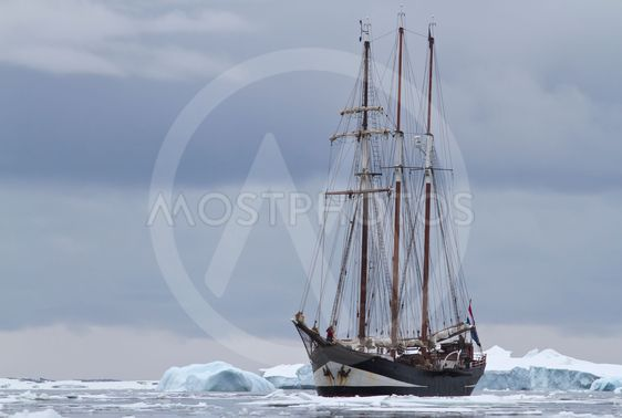 small sailing ship in Antarctic waters between ice floes...