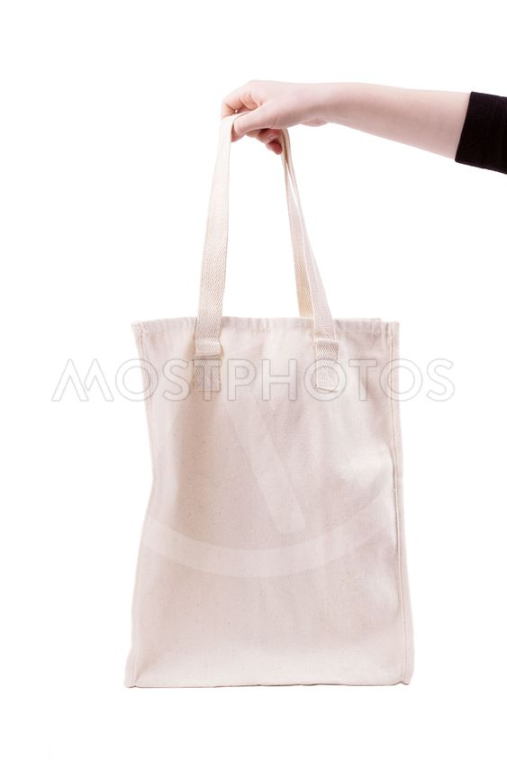 Mockup of female hand holding a blank tote canvas bag on...