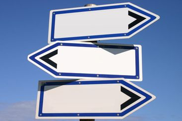 Blank three-way direction signpost with a blue sky...