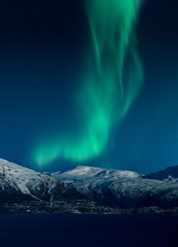 Northern lights above snow covered mountains and the...