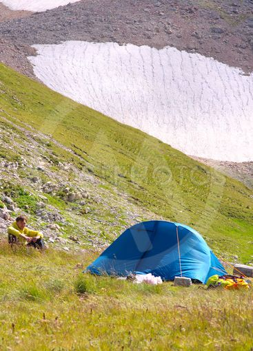 Camping Tent in Mountains with Man Hiker sitting on grass...