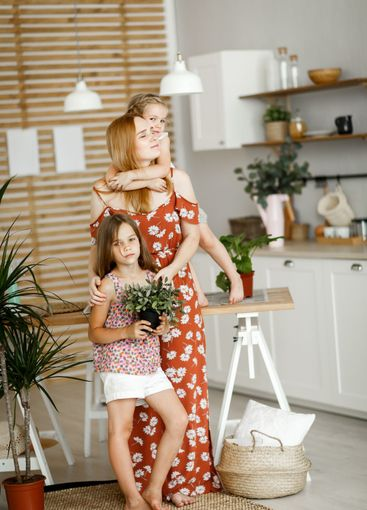 mom and daughters with indoor flowers in kitchen