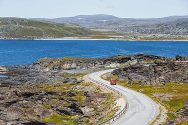 A red parcel delivery van on curvy road in norway