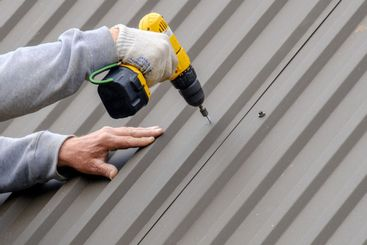 Male hands in gloves with a screwdriver screw the...