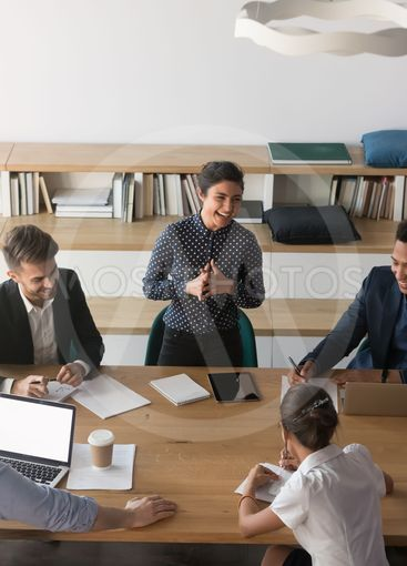 Multiethnic employees laugh discussing ideas at meeting