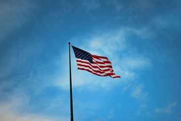 Waving flag of the United States in front of a cloudy...