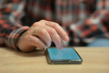 A Man is reading news on his cell phone