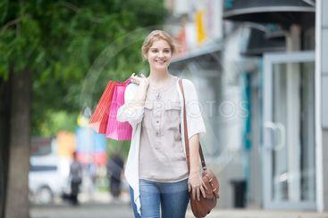 Portrait of young smiling woman enjoying shopping time