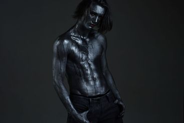 Man with nude torso covered with shimmering silver...