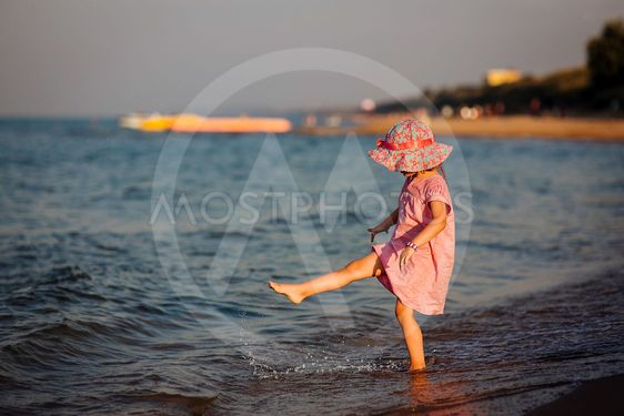 the girl creates splashes a foot at the sea