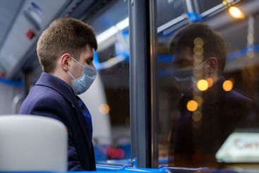 A man in a city bus wearing a protective medical mask...
