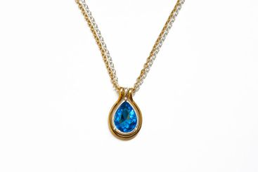 Silver gold necklace with a blue stone