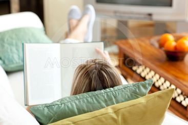Caucasian woman reading a book lying on a sofa