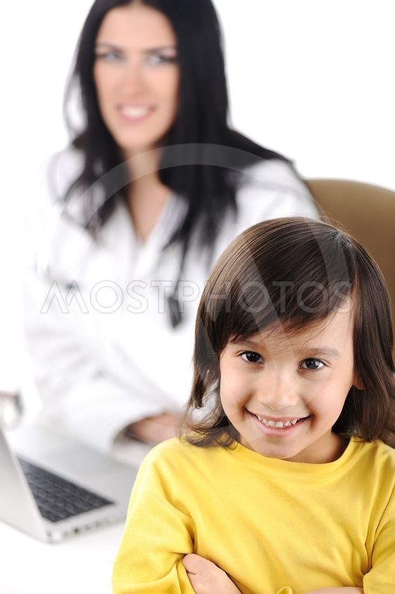 Young female doctor examining little cute child at modern...