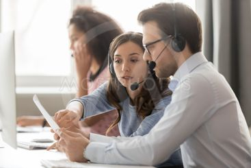 Call center agents in headsets discussing papers helping...