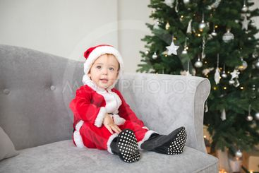 Baby in santa suit sit on sofa with Christmas tree