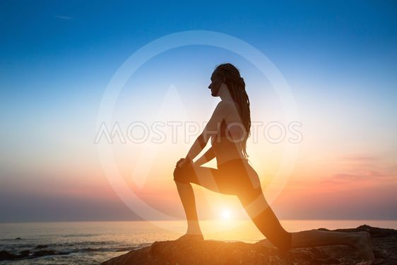 Silhouette fitness yoga women on the coast