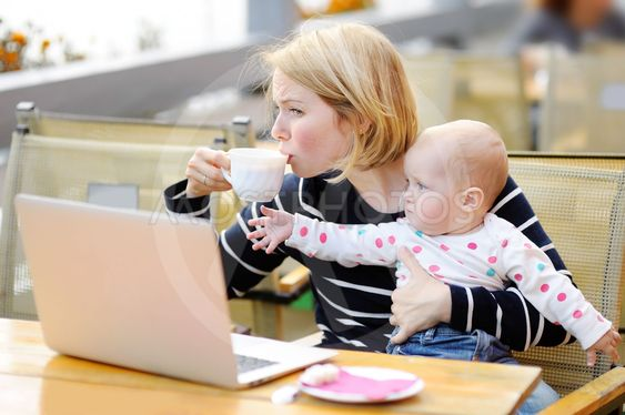 Tired young mother holding 6-month daughter and drinking...