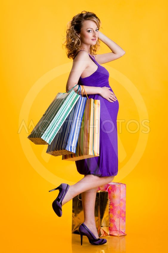 Beautiful pregnant woman holding shopping bags isolated...