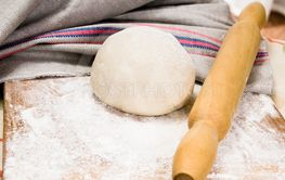 fresh raw dough and rolling pin
