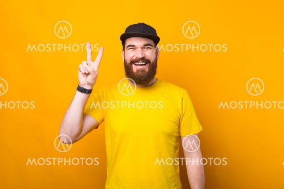 Photo of a cheerful young man is showing the peace sign...