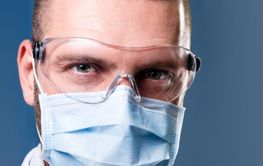 Doctor wearing medical protective mask and glasses...