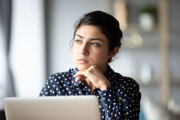 Pensive ethnic woman look in distance making decision