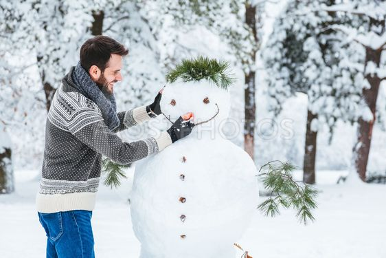 Young man making snowman in the park