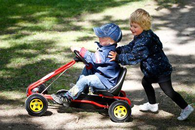 Två barn leker med trampbil 1
