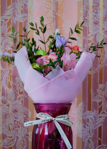 A delicate bouquet of different flowers in a light pink...